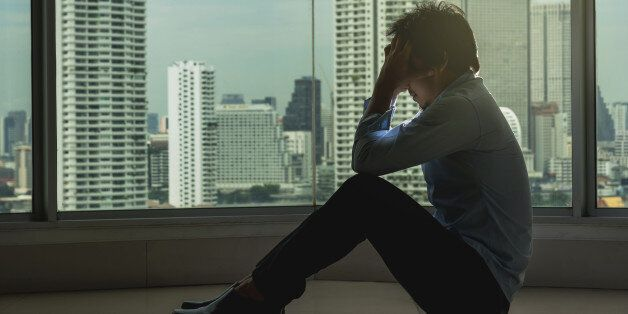 depressed man sitting head in hands on the interior Skyscraper with low light environment beside the...