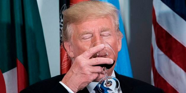 US President Donald Trump sips a glass after making a toast during a luncheon at the United Nations headquarters...