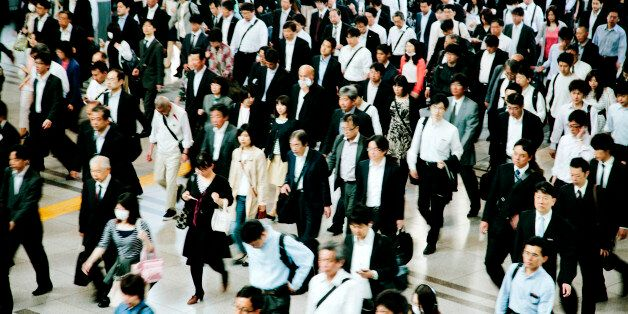 A busy pedestrian walkway, businessmen and women, walking to work, motion blurred, Tokyo. Horizontal