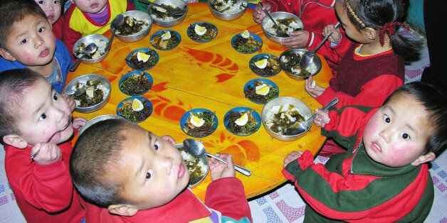 PYONGAN, NORTH KOREA - FEBRUARY 21: North Korean children eat lunch, including rice, provided by the...