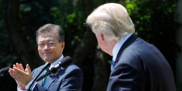 South Korean President Moon Jae-in (L) applauds next to U.S. President Donald Trump while delivering...