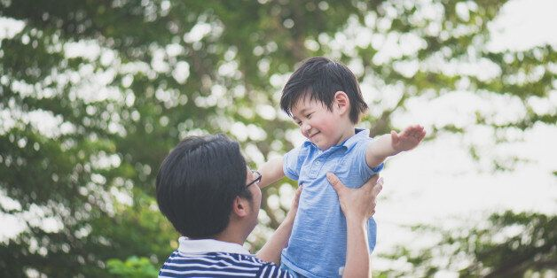 Asian father holding his son in the