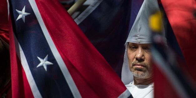 A member of the Ku Klux Klan looks on during a rally, calling for the protection of Southern Confederate...