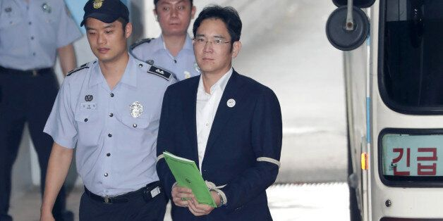 Jay Y. Lee, co-vice chairman of Samsung Electronics Co., right, is escorted by a prison officer as he...