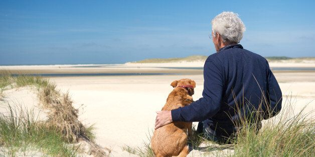 Man sitting with dog on sand dune at Dutch beach on wadden island