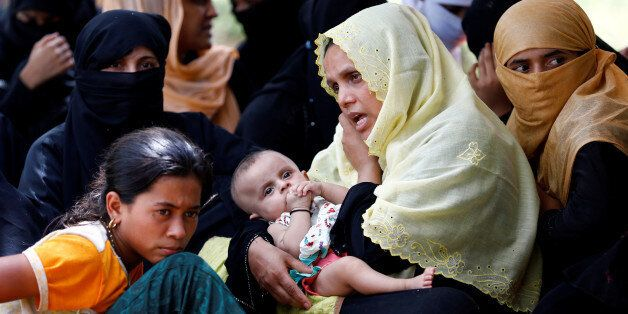 A Rohingya refugee woman with a child talks over phone as she takes shelter in No Man's Land between...