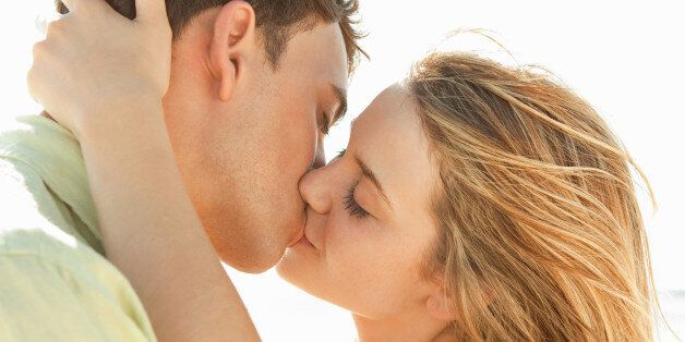 Romantic young couple kissing on a beach