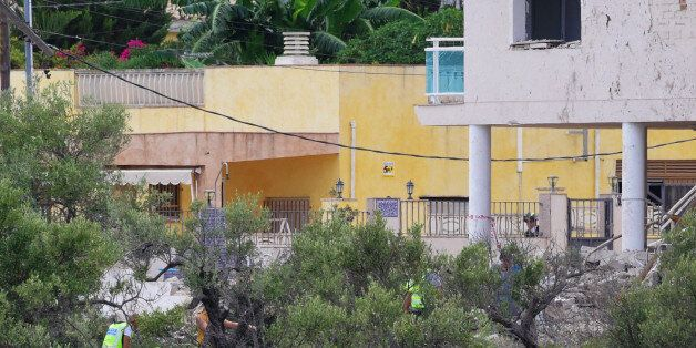 Investigators search the rubble of a house, where suspects of this week's twin assaults in Spain were...