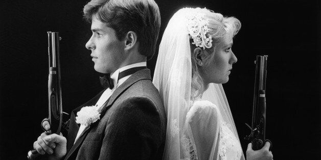 1980s BRIDE AND GROOM STANDING BACK TO BACK HOLDING DUELING PISTOLS (Photo by H. Armstrong Roberts/ClassicStock/Getty