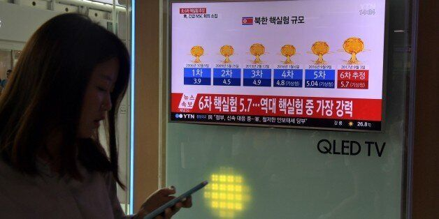 A woman walks past a television display at a train station in Seoul on September 3, 2017 showing a news...