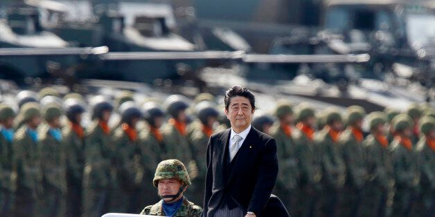 ASAKA, JAPAN - OCTOBER 23: Japanese Prime Minister Shinzo Abe, center right, inspects troops of the Self...
