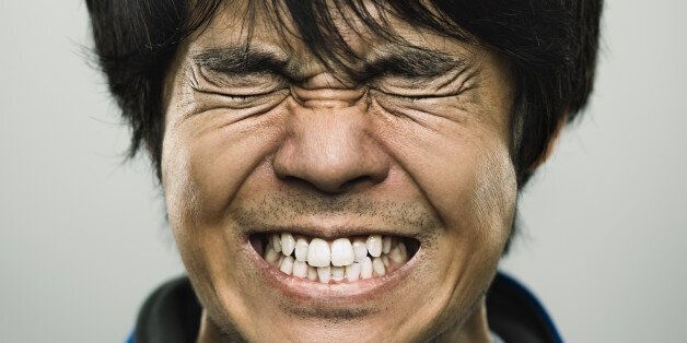 Studio portrait of a japanese young man with closed eyes and clenched teeth. The man has around 30 years...