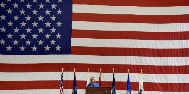 US Secretary of State Hillary Clinton listens for cheers from US troops during an event at Andersen Air...