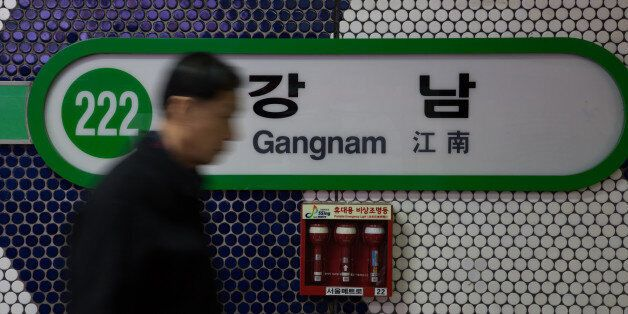 A man walks past signage for Gangnam subway station in Seoul, South Korea, on Thursday, Dec. 13, 2012....