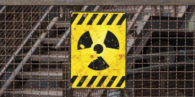 yellow radioactive warning sign on rusty