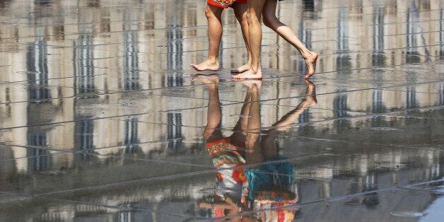 People cool off as they walk on a water mirror on the place de la Bourse in Bordeaux as hot summer temperatures...