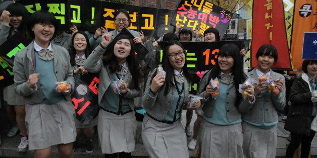 SEOUL, SOUTH KOREA - NOVEMBER 08: South Korean high school girls cheer for their senior classmates taking...