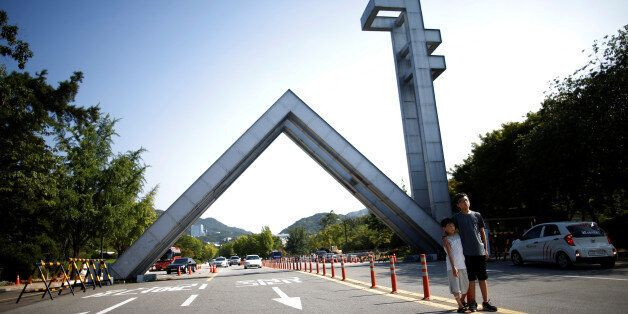 Children pose for photographs in front of Main Gate of the Seoul National University in Seoul, South...