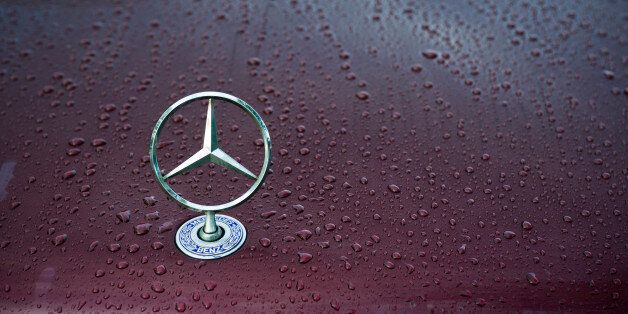'Padua, Italy - July 6, 2011: Mercedes classical logo on a wet car hood. Mercedes-Benz, a division of...