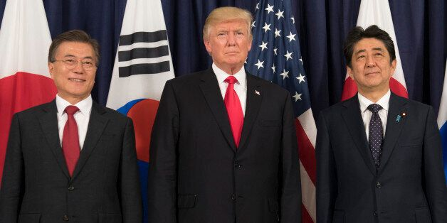 US President Donald Trump (C), Japanese Prime Minister Shinzo Abe (R) and South Korean President Moon...