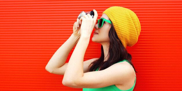 Fashion pretty cool girl wearing a colorful clothes with old retro camera shooting in the