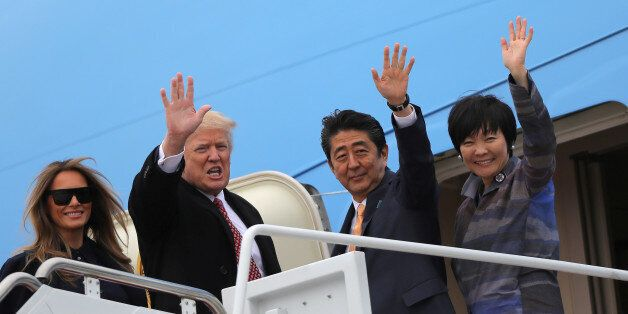 U.S. President Donald Trump and his wife Melania (L) wave with Japanese Prime Minister Shinzo Abe (2nd...