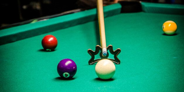 Young and pretty woman using bridge stick to hit cue ball during pool