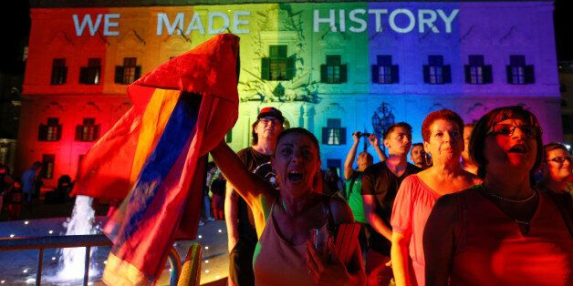 People celebrate in front of the rainbow-colour lit Auberge de Castille, the office of Prime Minister...
