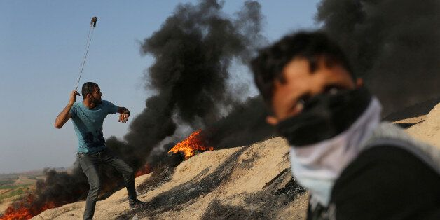 A Palestinian protester uses a sling to hurl stones towards Israeli troops during clashes near the border...