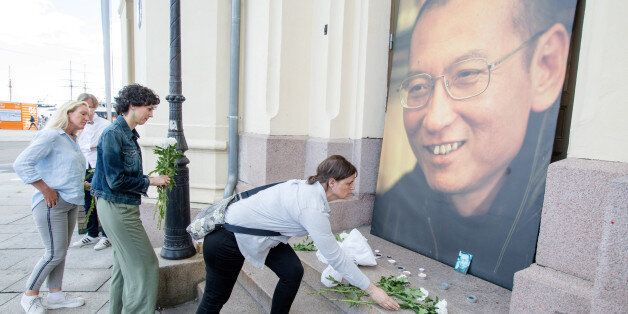 People place flowers and light candles in front a picture of late Nobel Peace Laureate Liu Xiaobo outside...