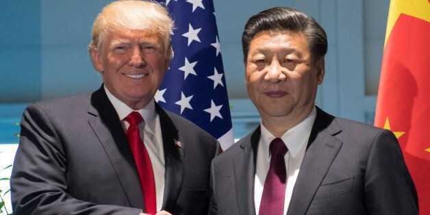 U.S. President Donald Trump and Chinese President Xi Jinping (R) shake hands prior to a meeting on the...