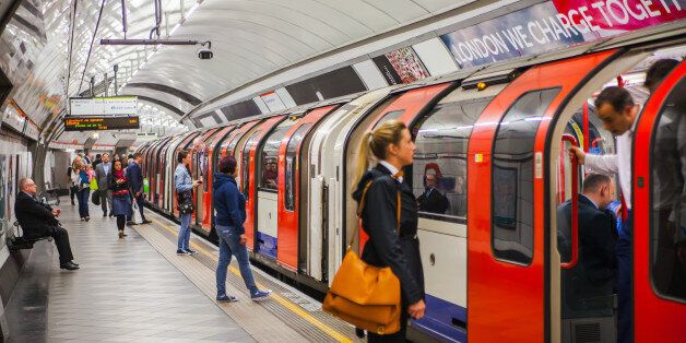London, UK - April 22, 2015: People waiting at underground tube platform for train