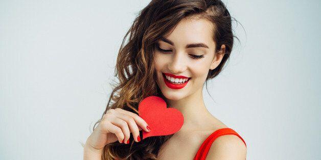 Studio shot of young beautiful woman holding artificial heart. Professional