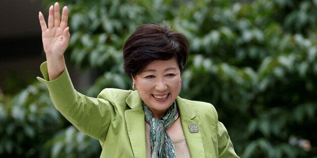 Tokyo Governor and head of Tokyo Citizens First party Yuriko Koike waves to voters atop of a campaign...