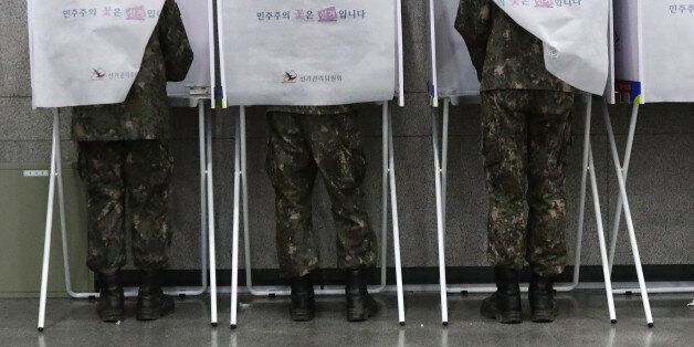 SEOUL, SOUTH KOREA - MAY 04: South Korean soldiers casts their preliminary vote in a polling station...