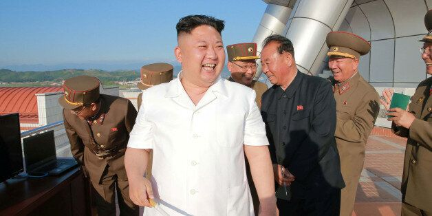 North Korean leader Kim Jong Un reacts after doing a test-fire of new cruise rocket in this undated photo...