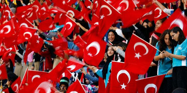 Imam Hatip religious school students wave national flags as they wait for arrival of Turkish President...