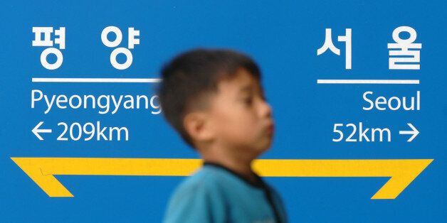 SOUTH KOREA - OCTOBER 08: A South Korean child walks past a sign which indicates the distance between...