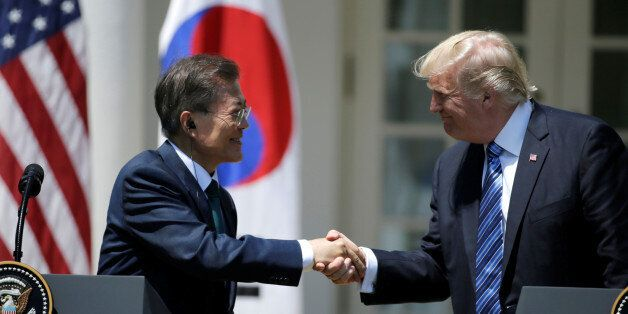 U.S. President Donald Trump (R) greets South Korean President Moon Jae-in prior to delivering a joint...
