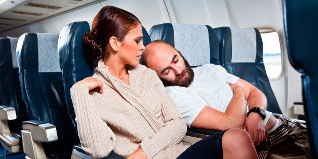 Disgusted woman looking at the sleeping man sitting next to her, who rests his head on her