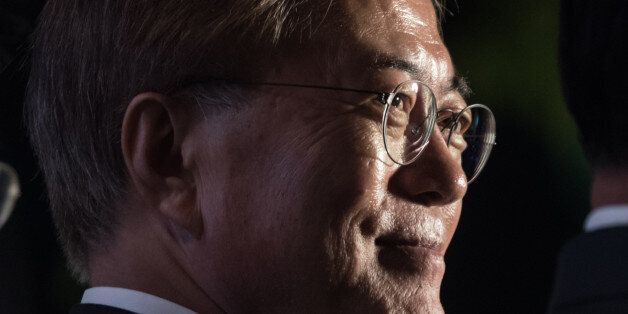 South Korean presidential candidate Moon Jae-In stands on a stage to greet supporters after exit polls...