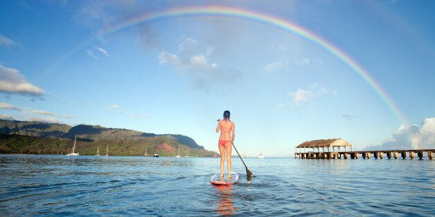Stand up paddle board in hanalei bay with rainbow in Kauai, Hawaii,