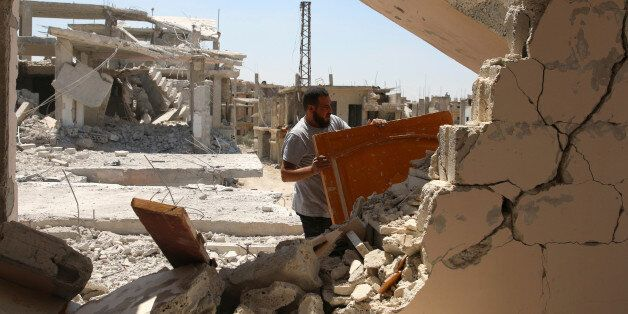 A man gathers his belongings from damaged houses inside a former Palestinian refugee camp in a rebel-held...