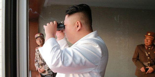 North Korean leader Kim Jong Un looks on during a ballistic rocket test-fire through a precision control...