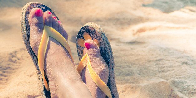 Young girl legs and flip-flop on the sand beach in