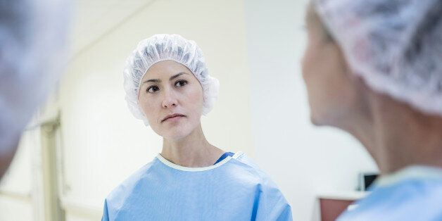 Female nurse talking to colleague. Medical professional wearing surgical clothing discussing with
