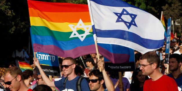 Participants hold flags during the gay pride parade in Jerusalem July 29, 2010. This year's parade marks...