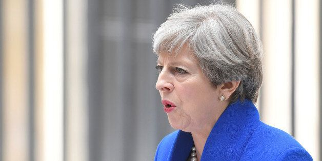 Britain's Prime Minister Theresa May makes a statement in Downing Street after traveling to Buckingham...