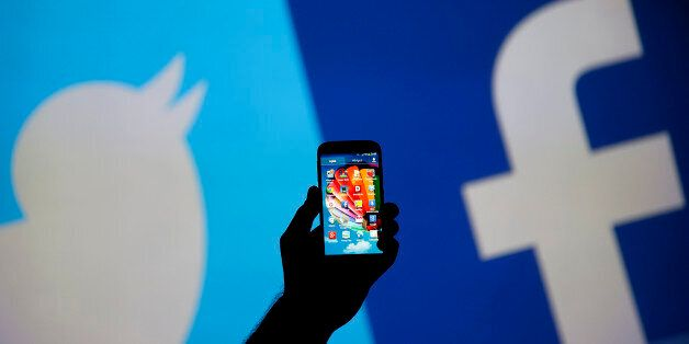 A man holds up a Samsung S4 smartphone against a video screen with Twitter and Facebook logos in this...