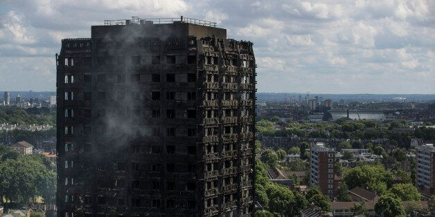 LONDON, ENGLAND - JUNE 15: Debris hangs from the blackened exterior of Grenfell Tower on June 15, 2017...